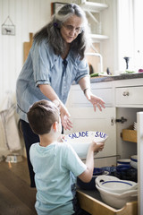 Boy giving utensil to grandmother in kitchen at home