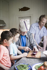 Grandsons looking at grandfather cutting onion on board while father working in kitchen