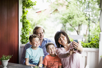 Mother taking selfie with family in porch