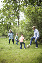 Family playing soccer in back yard