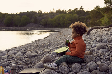 Side view of boy drinking while sitting on rocks at beach during sunset