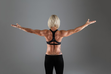 Back view portrait of a muscular adult sportswoman