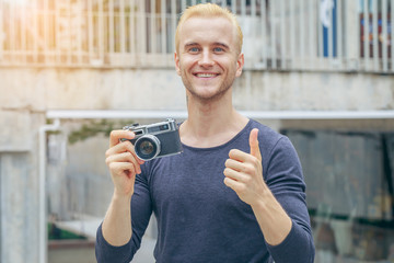 Young man with vintage photo camera, Street photo, Travel Lifestyle vacations concept