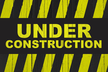 Under construction warning sign with yellow and black stripes painted over cracked wood. Sign usually used in construction sites meaning: do not enter the area, caution, danger