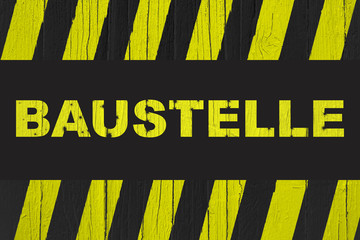 Baustelle (in German, construction site) warning sign with yellow and black stripes painted over cracked wood.