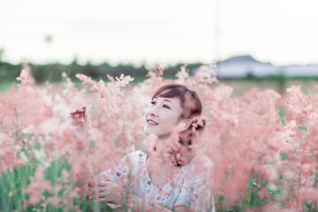 Beautiful young Asian women around the age of 30-40 years travelers feels happy and freedom Amid the Garden flowers pink grass in his holidays During his time at sunset .