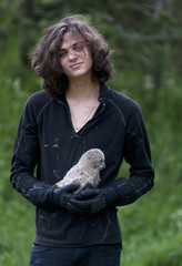 Portrait of smiling young man holding owl while standing in forest