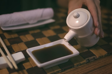 The girl sits at the table in cafe and pours soy sauce from a jug into a bowl and prepares to sushi. Asian food.