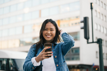 Portrait of smiling teenage girl using smart phone against building in city