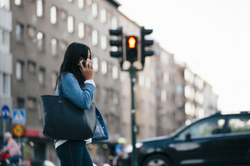 Side view of teenage girl talking on smart phone while walking against building in city