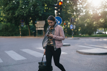 Young woman crossing street while using smart phone in city