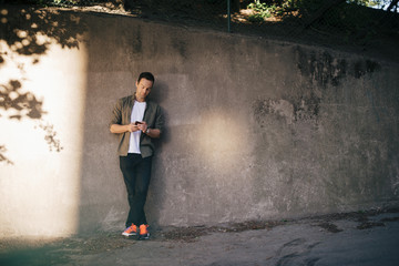 Man standing against wall while using smart phone