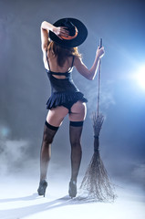 Background to Halloween, sexy woman in a witch costume with a broom, view from the back.