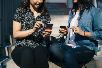 Mid section of female friends using a smart phones while sitting