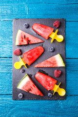 Photo of watermelon slices , fruit ice, blueberries on cutting board