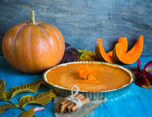 Pumpking pie on blue wooden desk. Homemade pie. Thanksgiving dinner. Autumn