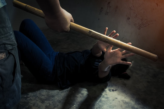 Man with wood in hand is abusing his wife, woman covering in the corner at home - domestic violence concept