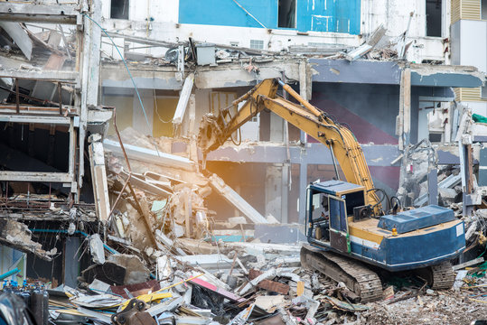 Worker controlling backhoe demolishing old buildings. Demolition site with pile of rubble and bulldozer at Bangkok site.