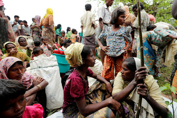 Rohingya refugees, who crossed the border from Myanmar two days before, rest while they walk to the refugee camps, in Palang Khali