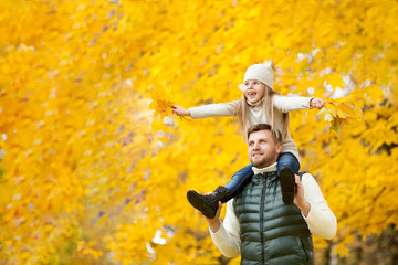 Portrait of happy father holding their daughter on shoulders, with leaves in handson the autumn park