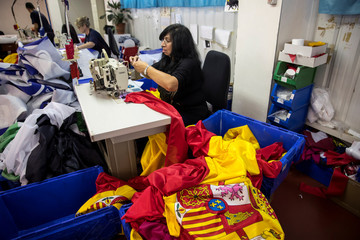 An employee sews Spanish flags at a factory in Colmenar Viejo