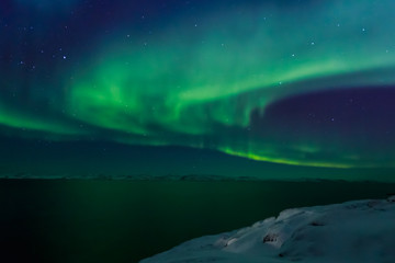 Spiral green Northern lights shining over the fjord with mountains in the background, Nuuk, Greenland