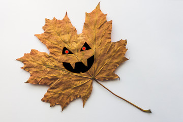Single yellow autumn leaf with Halloween face on a white bacground