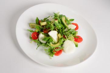 Salad of mozzarella, avocado, cherry tomatoes and arugula in a plate