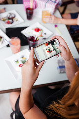 Social media food picture. Modern lifestyle. Unrecognizable female in cafe. Mobile technology in focus on foreground, popular behavior, style concept