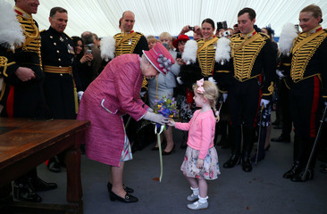 Britain's Queen Elizabeth receives a posy from Tilly Beau Wildish during a reception following The King's Troop Royal Horse Artillery 70th parade in Hyde Park in London
