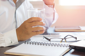 businessman holding glass of water and removing glasses on table, relax and healthy concept.