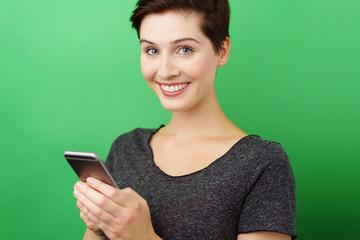 attraktive frau mit smartphone vor grünem hintergrund