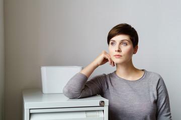 junge geschäftsfrau steht nachdenklich im büro