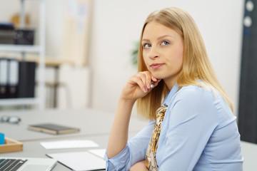 junge frau im büro schaut mit ernstem blick zur seite