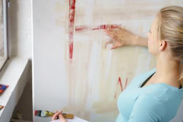 junge malerin wischt mit der hand über ein bild