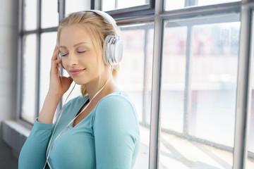 frau steht entspannt am fenster und hört musik