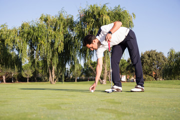 Man leaning on club and putting golf ball on ground