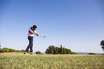 Man in polo shirt performing powerful swing while playing golf on sunny day.
