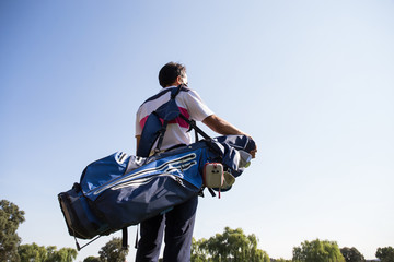 Man in polo shirt standing on golf course with golf bag on his shoulder.