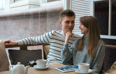 Young nice couple sitting in cafe wrapped in cozy blanket drinking tea. Love story of a girl and a boy. Man and woman embrace one another on a terrace. Sweet couple choosing what to read on a tablet.