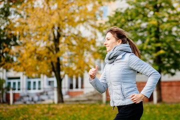 Young sporty woman jogging in autumn.
