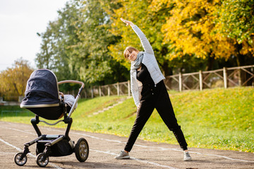Young smiling sporty woman with baby stroller in warm clothes warming up - doing stertching exercises in track of stadium. Autumn, fall and motherhood concept.