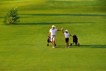 Stores à enrouleur Golf man with his son golfers walking on perfect golf course at summer evening