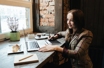 Young beautiful woman working on a graphic tablet, retouching photos after photography. Business lady having a break, making decisions. Modern girl designing mobile applications and web sites.