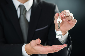 key chain with key in hand of a real estate agent