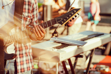guitarist sets up an electric guitar before the concert begins on the street,filter applied