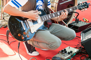 guitarist sets up an electric guitar before the concert begins on the street