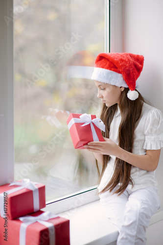 7316be1daf686 cute little girl in Santa hat dreaming by the window holding gif ...