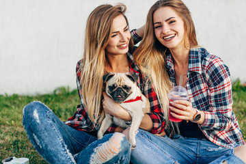 Two beautiful smiling sisters twins and dog pug sitting on green grass in the summer park