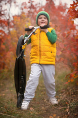A boy rides a scooter in the autumn Park.